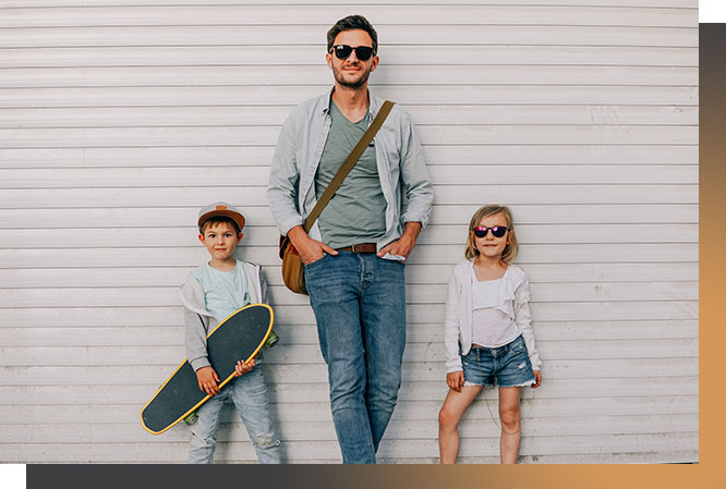 Dad, son, and daughter posing for picture against a white background